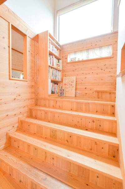 踊り場に本棚のある幅広のリビング階段