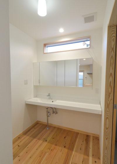 ミラーキャビネットとマーブライトカウンターのある洗面室